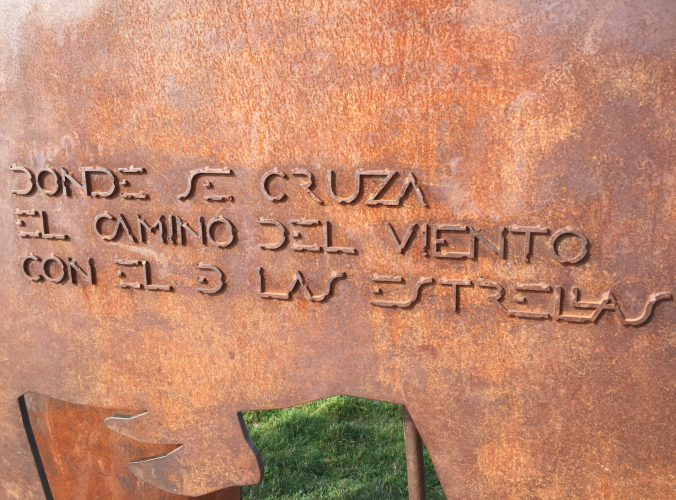 """Signage at the Alto de Perdón monument very roughly translated """"where the path crosses the place where the wind meets the stars."""""""